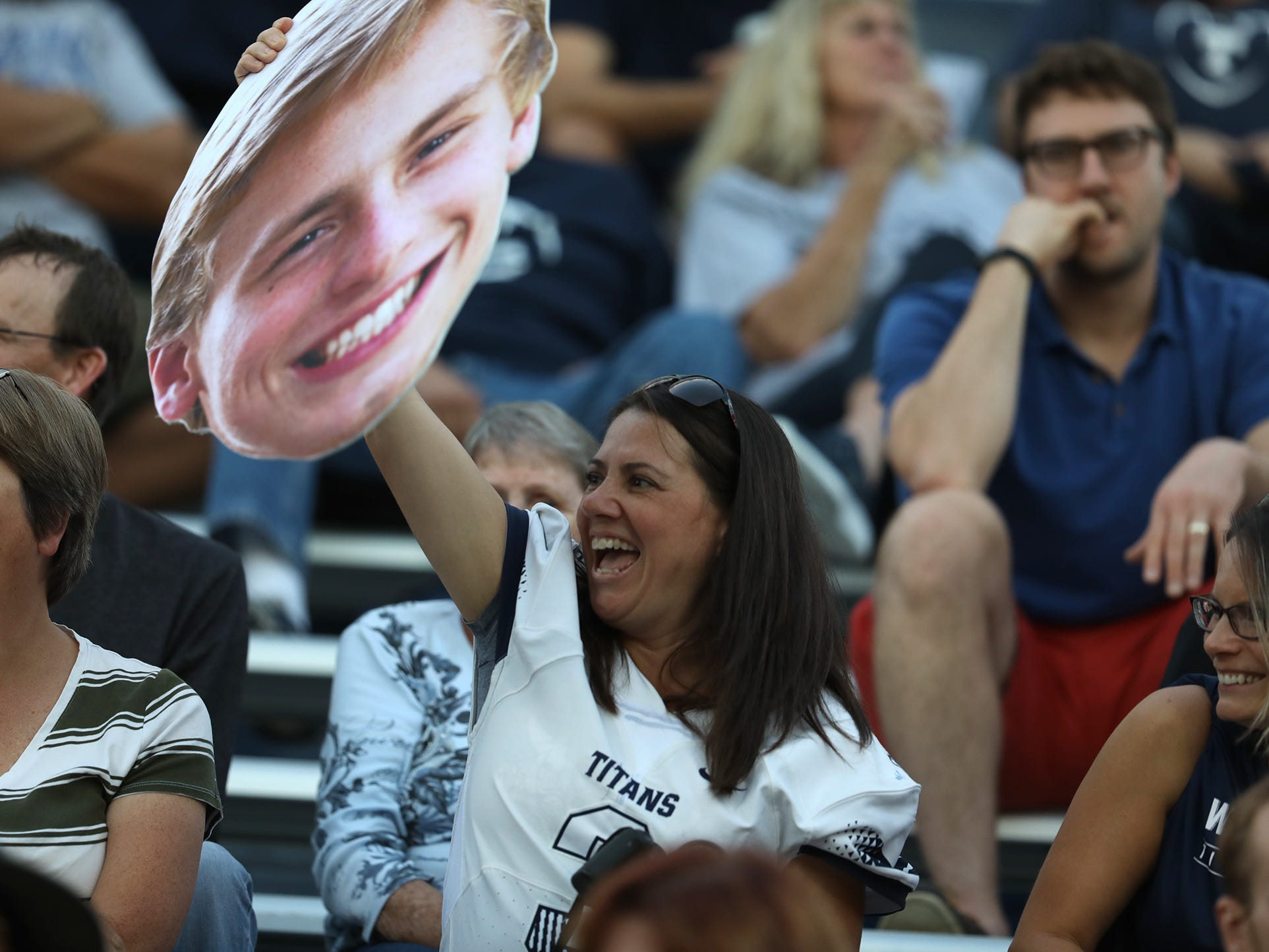 Nichole Canfield, holds up a large photo of her son, Jake Canfield, who is the quarterback of Webster Thomas football team, and waves it to someone in the stands during Friday night's game against Greece Athena.