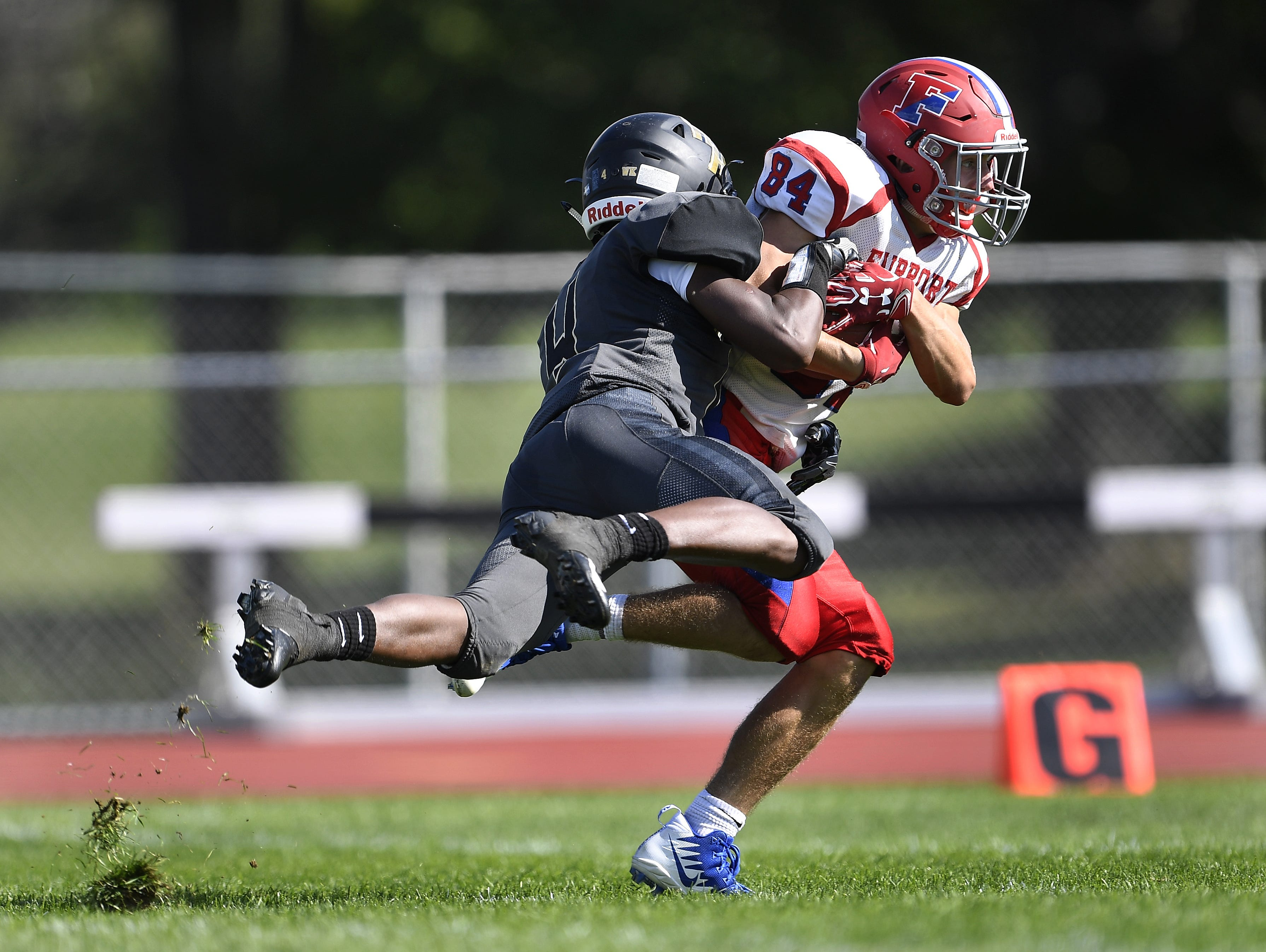 Fairport's Ryan Harman, right, is tackled by Rush-Henrietta's Mark Rogers after a 71-yard catch to open the second half Saturday, Sept. 15, 2018.