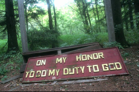 Oct. 9, 1996: Girl Scout motto is propped on what remained of an outdoor stage at Camp Beechwood.