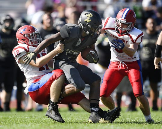 Fairport's Andrew Copeland, left, tackles Rush-Henrietta's Willie Walker as Fairport's Gavin Ingalls, right, closes on the play Saturday, Sept. 15, 2018.