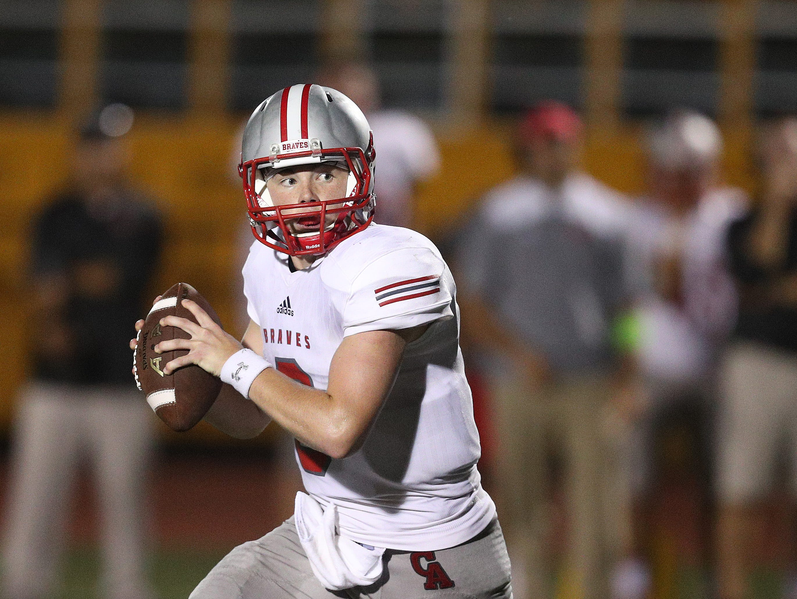 Canandaigua quarterback Jack Johnston rolls to his right looking downfield.