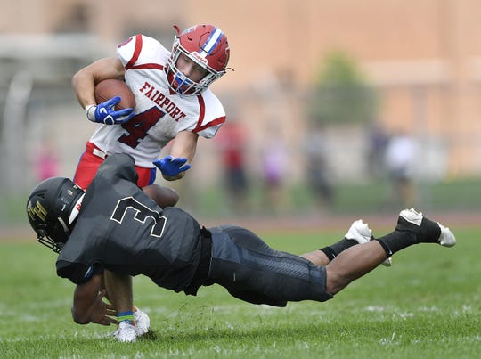 Fairport's Dante Coccia, top, is tackled by Rush-Henrietta's Rayshod Walker on Saturday, Sept. 15, 2018.