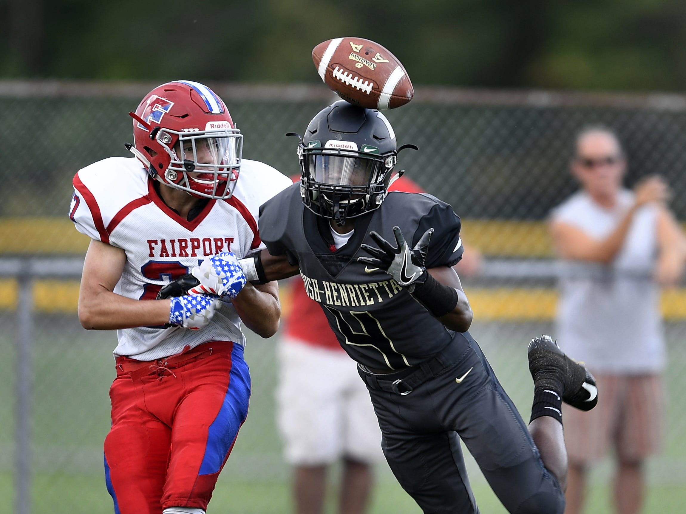 Rush-Henrietta's Mark Rogers, right, can't quite haul in this pass while defended by Fairport's Mason Gasbarre on Saturday, Sept. 15, 2018.
