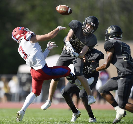 Rush-Henrietta's Tanner Clark, center, breaks up a pass intended for Fairport's Sam Eigan. It was then intercepted by Rush-Henrietta's Devin Felder, right, Saturday, Sept. 15, 2018.