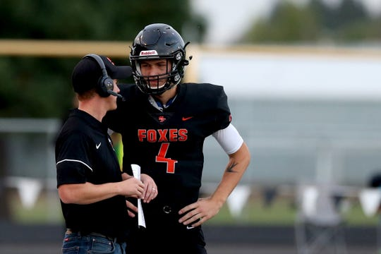 Silverton's Levi Nielsen (4) talks with head coach Josh Craig in the first half of the Lebanon vs. Silverton high school football game in Silverton on Friday, Sep. 14, 2018.