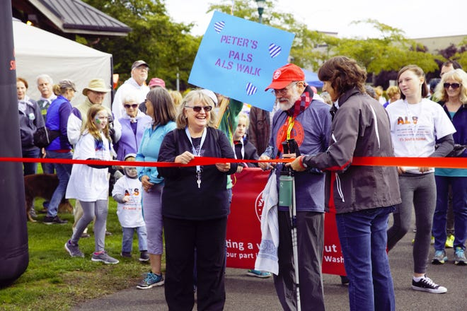 Vernadene and Peter Anderson, who was diagnosed with ALS in 2017, cut the ribbon at the Walk to Defeat ALS event at Riverfront Park Saturday, Sept.15, 2018.