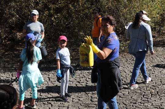 Lina Cabrera shows Closter Park's Girl Scouts troop an oil container found at Upper Carr Lake.