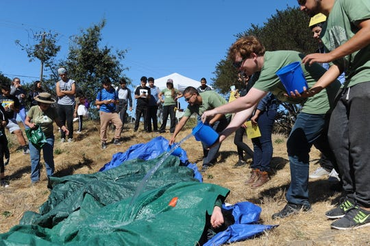 CSUMB students and Return of the Natives Director Laura Lee Lienk conduct a watershed model for Salinas students on Saturday.