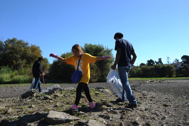 Alisal High School students Diego Vazquez, left, and Ricardo Sumano, right, clean-up Upper Carr Lake in Salinas with Sumano's little sister Isabela, center, on Saturday.