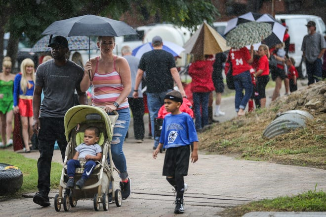 Residents walk with umbrellas during River Fest Saturday, Sept. 15, 2018, in the Bosque.
