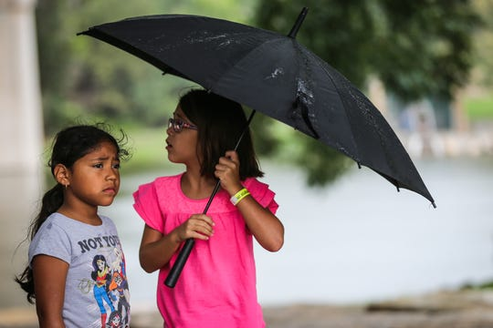 Yoselynn Fuertes, 7, and Hayley Bobholz, 8, walk around with an umbrella during River Fest on Saturday, Sept. 15, 2018, in the Bosque.