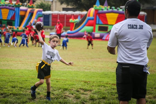 Kids practice flag football before the game during River Fest Saturday, Sept. 15, 2018, in the Bosque.
