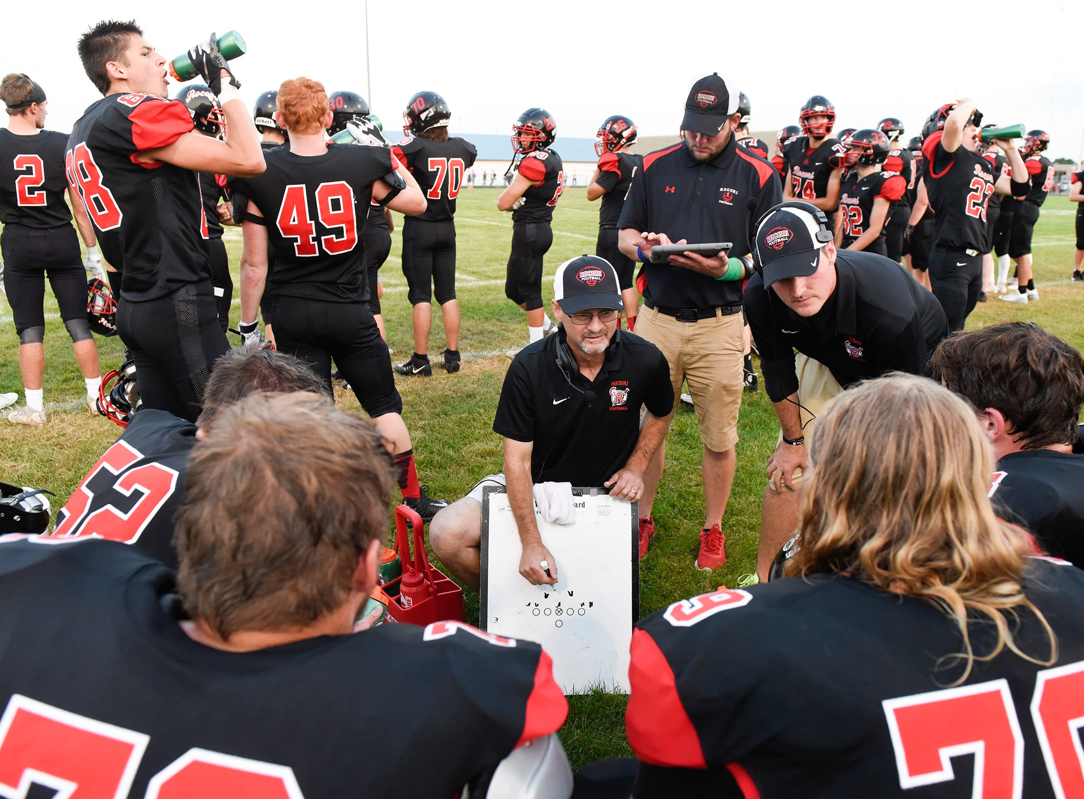 ROCORI players and coaches talk on the sidelines.