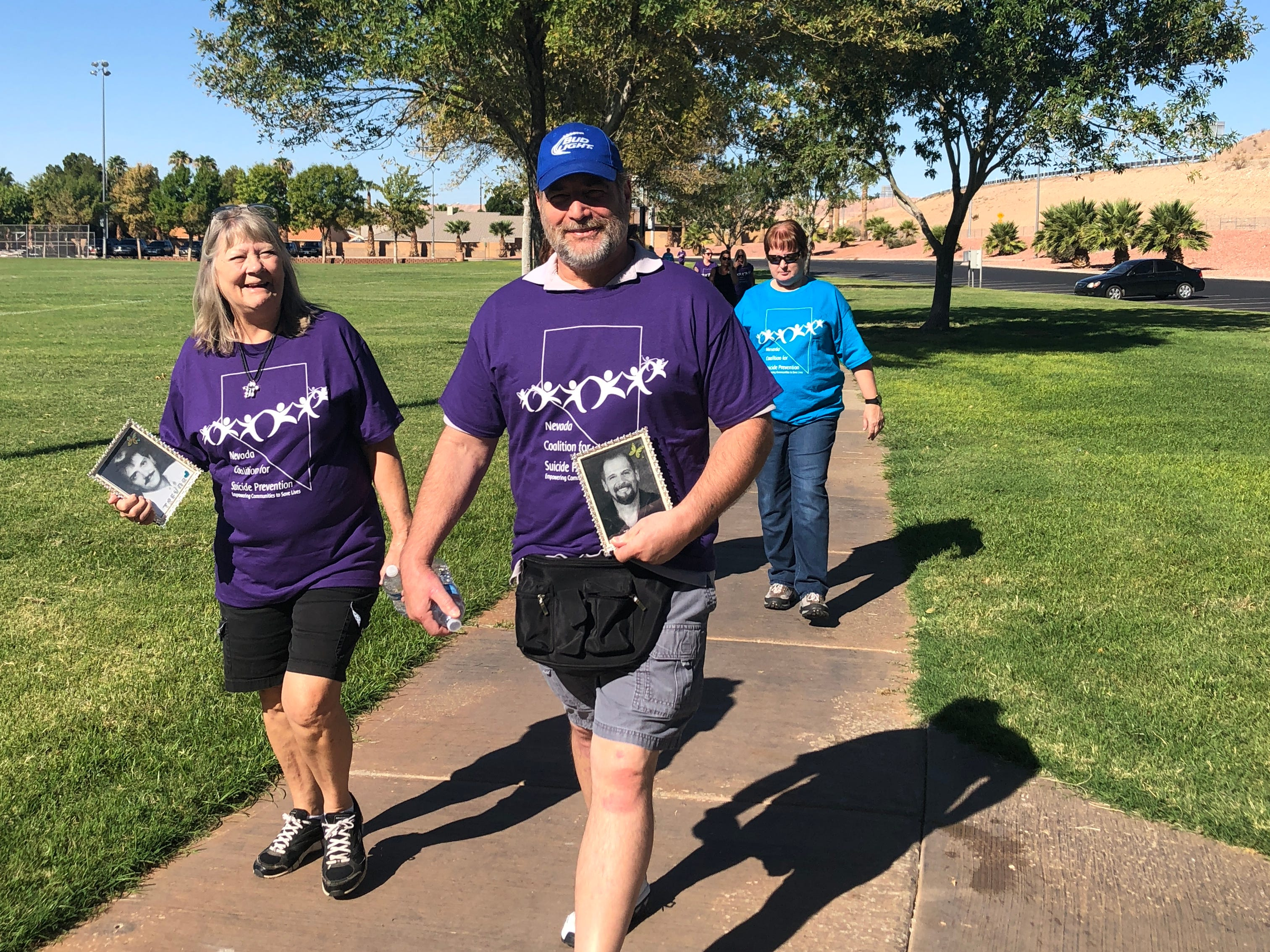Residents holding photos of loved ones participate in the Walk in Memory, Walk for Hope suicide-prevention community event at the Mesquite Recreation Center on Sept. 15, 2018.