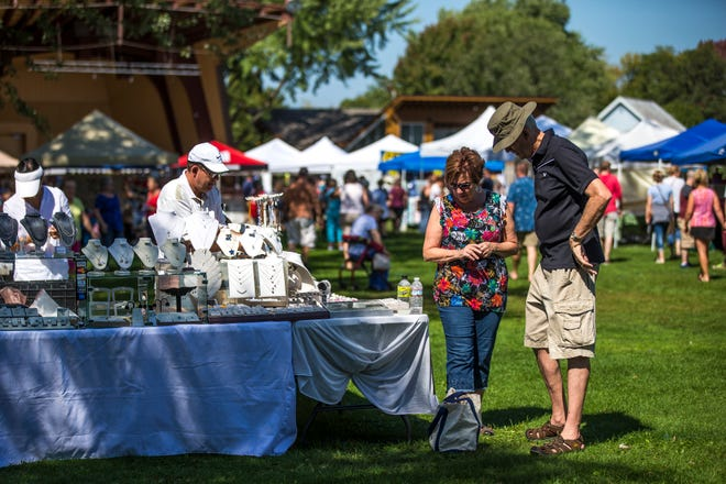 Shoppers examine jewelry on display at Art in the Park in Stevens Point, Wis.
