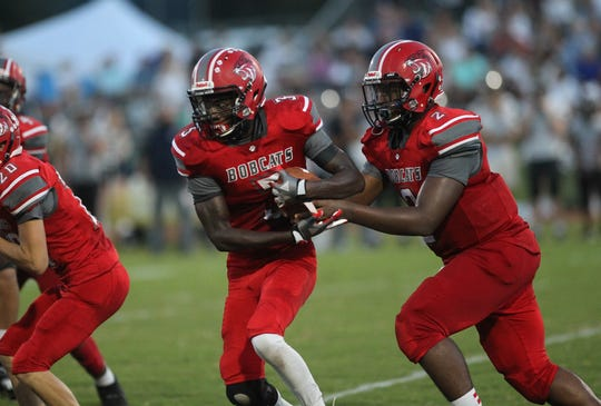 Munroe's Julian Harrison takes a hand off from quarterback Xavier Gray during a game earlier this year.