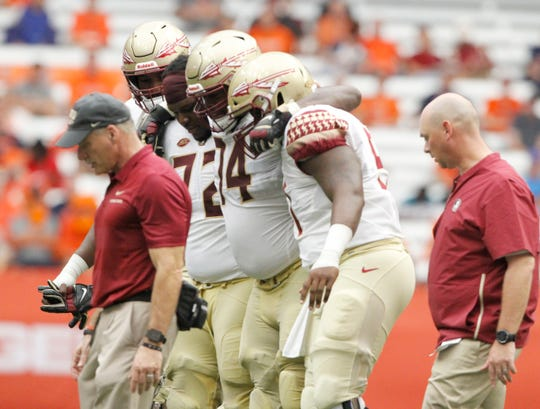 Florida State players help their teammate Derrick Kelly II, center, to the bench after he was injured in the fourth quarter of an NCAA college football game against Syracuse in Syracuse, N.Y., Saturday, Sept. 15, 2018. Syracuse won 30-7. (AP Photo/Nick Lisi)
