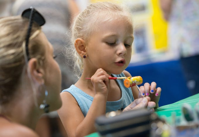 """Lisa Rufolo (left) helps her daughter Ava Rufolo, 3, both of Jupiter, paint a cork that will be used to make a cork wreath that is to be featured at the Children's Ball, during the Autumn Adventure event at The Children's Museum of the Treasure Coast on Saturday, Sept. 15, 2018 in Jensen Beach. """"We are having fun,"""" said Lisa Rufolo adding, """"This museum is great and we will have to come again."""""""