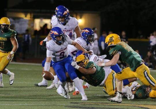 Westlake High quarterback Patrick Roberg is taken down by Moorpark's Anthony Gomez during a game earlier this season. The Warriors play in the Division 2 playoffs, while Moorpark is in Division 3.