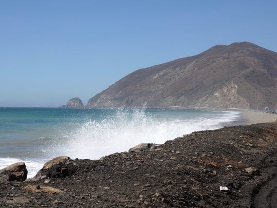 STAR FILE PHOTO Waves crash onto the shoulder of Pacific Coast Highway south of Mugu Rock.