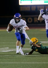 Moorpark High's Ethan Gomez tries to keep Westlake's Tyler Enderle from getting away during Friday night's game.