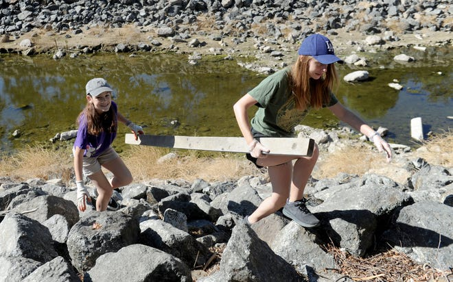 Alissa Reese and Hayden Kelly from Girl Scout Troop 60844 retrieve a board in the Arroyo Simi Greenway in Simi Valley during the 2018 Coastal Cleanup Day.