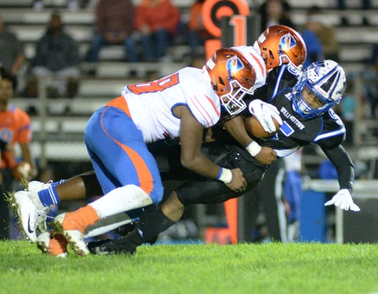 A duo of Millville players bring down Williamstown's Wade Inge during the second half at Williamstown High School, Friday, Sept. 14, 2018.