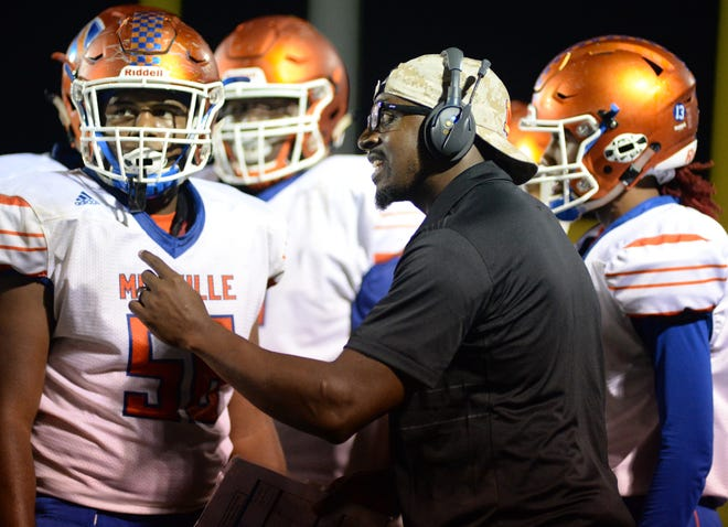 Millville's head coach Dennis Thomas talks with his players during the first half against Williamstown at Williamstown High School, Friday, Sept. 14, 2018.