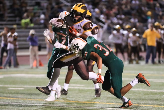 Golden West's Lonnie Wessel (4) rushes past Porterville's Jovanie Cardenas (32) to score a TD during a non-league high school football game at Jacob Rankin Stadium on Sept 14th, 2018.