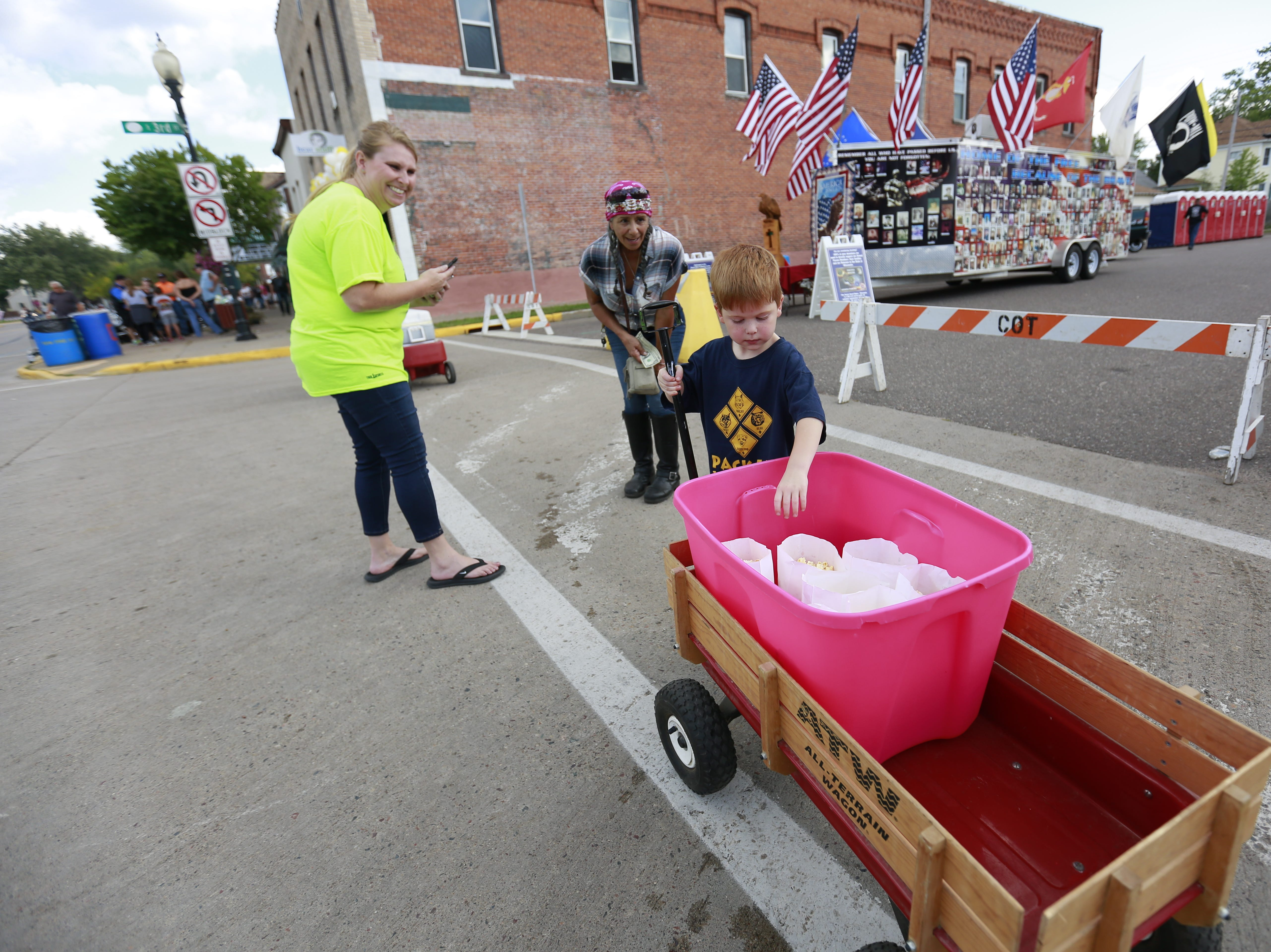 Brod Younker, right, sells popcorns for his scout troop 548 during the 37th Annual Tomahawk Fall Ride Friday, Sept. 14, 2018, at downtown Tomahawk, Wis. T'xer Zhon Kha/USA TODAY NETWORK-Wisconsin
