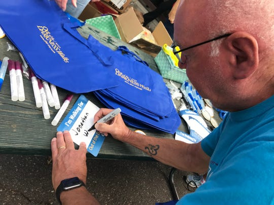 Steve Wesener writes his son's name on a sign worn by participants of the Out of the Darkness suicide prevention walk.