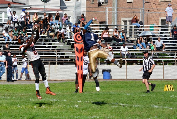 White Plains running back Josiah Harris pull down a late fourth-quarter touchdown over Yonkers Force defensive back Rance Hamilton.