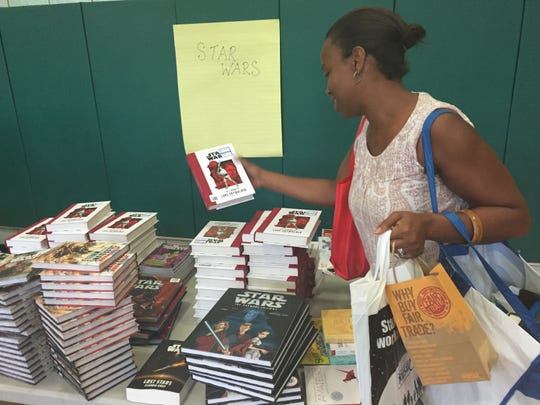 """Nadine Thomlinson checks out a book Saturday at the """"First Book"""" program at Trinity Elementary School in New Rochelle. """"These are classics,"""" she said about the """"Star Wars"""" franchise. She has two children in the school district."""
