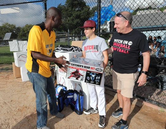 Evan Schiff, 12, from Scarsdale, center, helps Dwayne Brown, the president of the Mount Vernon RBI (Reviving Inner-city Baseball), left and David Rhode,, the CEO of Pitch in for Baseball and Softball, unpack boxes of baseball gear before a game at Brush Park in Mount Vernon, Sept. 15, 2018. Schiff, as part of his bar mitzvah project, raised $9,000 from friends and family and with the help from the organization was able to deliver $20,000 worth of gear to Mount Vernon.