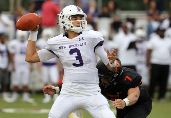 New Rochelle quarterback Mac Coughlin (3) looks to pass as Mamaroneck's Charlie Parkinson (7) charges him during the first-half of their football game at Mamaroneck High School Sept. 14, 2018.