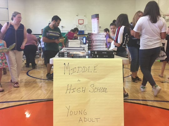 """A banquet table stacked with books at the """"First Book"""" program Saturday at Trinity Elementary School in New Rochelle."""