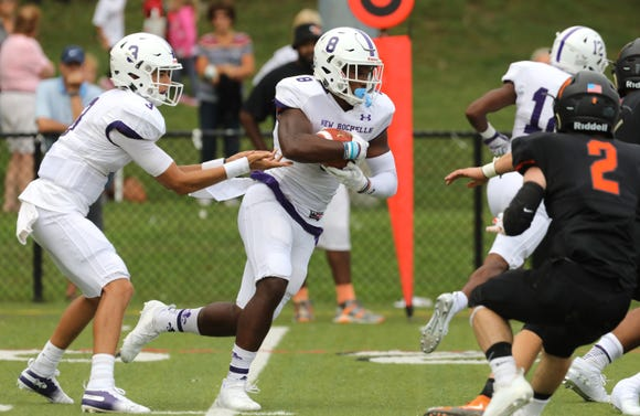 New Rochelle quarterback Mac Coughlin (3) hands it to Jordan Forrest (8) during first-half action of their football game against Mamaroneck at Mamaroneck High School Sept. 14, 2018. New Rochelle won, 48-7.