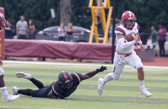 Stepinac quarterback Joey Carino breaks from of Iona Prep's Keshawn McDowell as he scrambles for yardage during a varsity football game at Iona Prep in New Rochelle Sept. 15, 2018. Iona Prep defeated Stepinac in overtime 36-34.