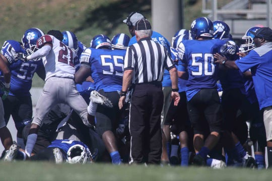 Players from Howard (in blue) and Hodgson fight during the second quarter on Saturday at Baynard Stadium. No fans were involved, and after a 13-minute delay the game resumed. Hodgson won 43-26.