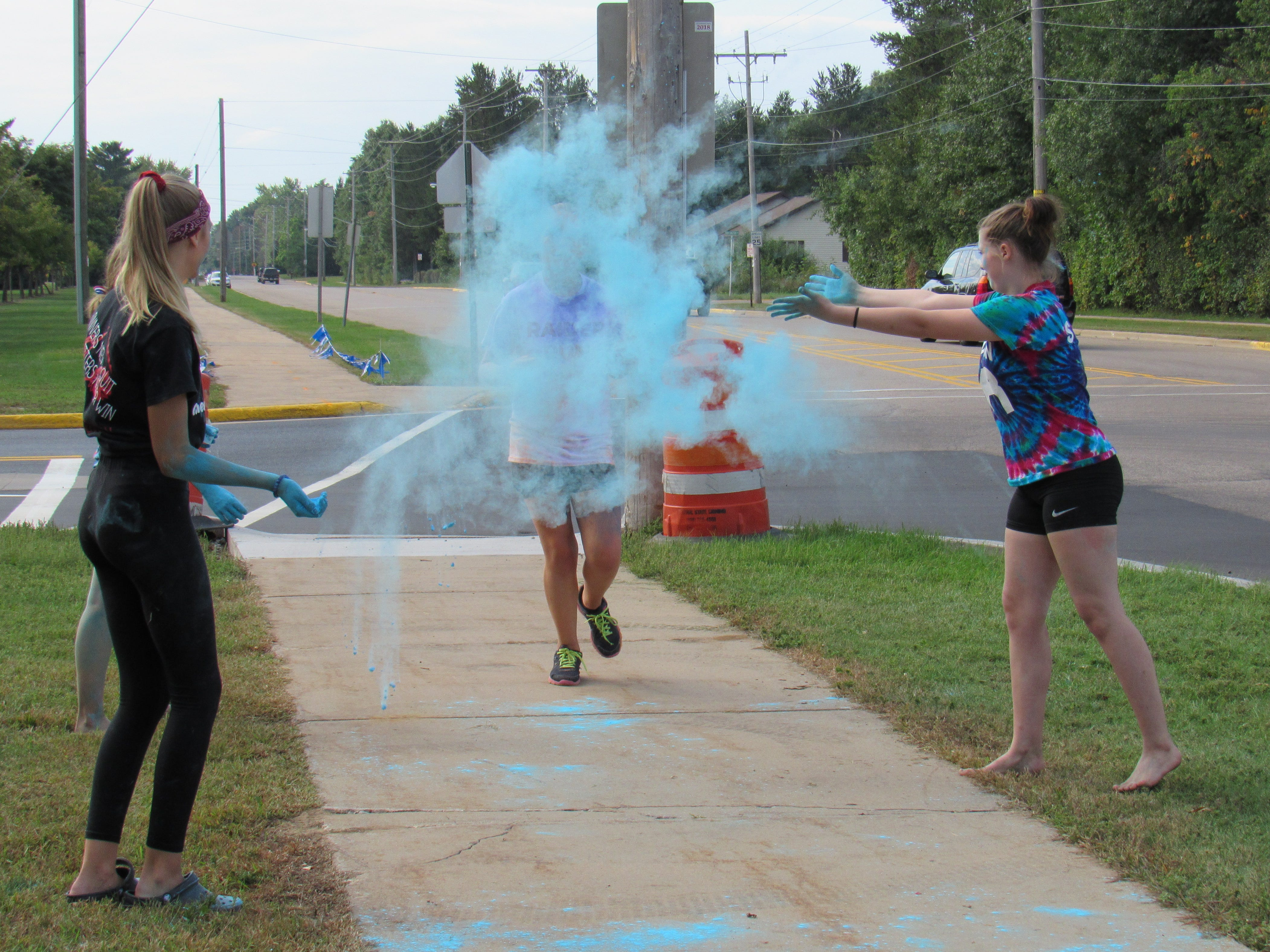 Participants run through a blue color station during the Lincoln High School Cheer & Stunt Color Run Saturday, Sept. 15, 2018, in Wisconsin Rapids.