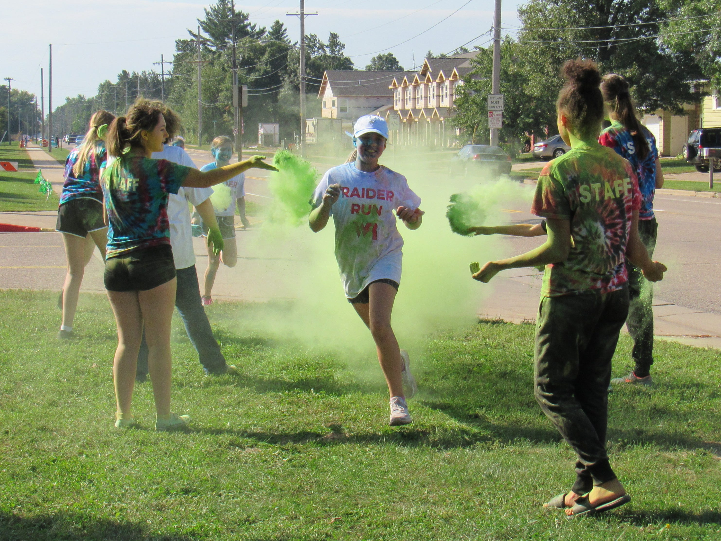 Participants run through a green color station during the Lincoln High School Cheer & Stunt Color Run Saturday, Sept. 15, 2018, in Wisconsin Rapids.