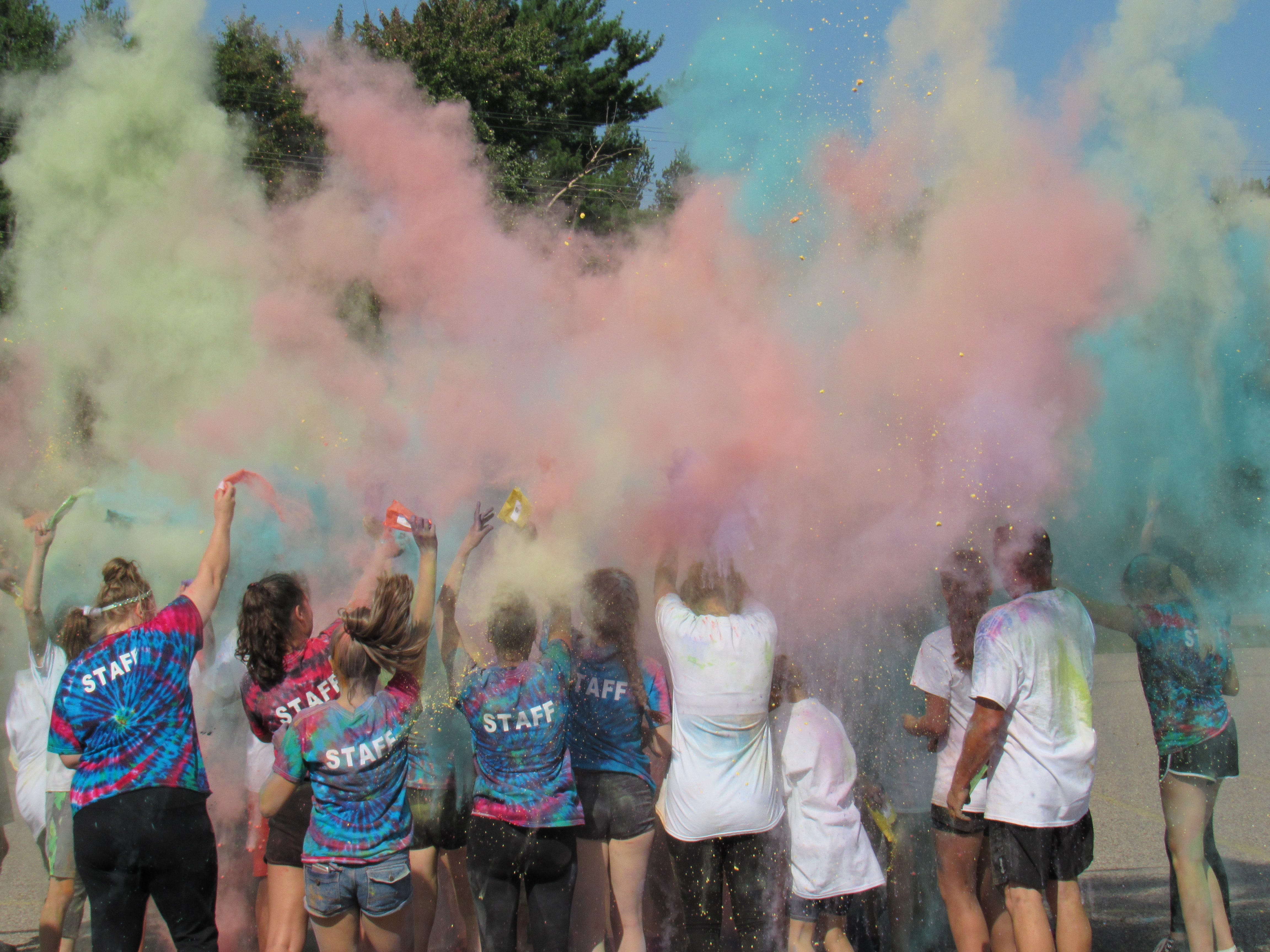 Participants toss colored cornstarch into the air at the end of the Lincoln High School Cheer & Stunt Color Run Saturday, Sept. 15, 2018, in Wisconsin Rapids.