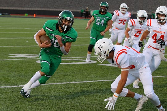 Brendin Fallon runs for extra yards  Friday evening in Iowa Park as the Hawks hosted the Burkburnett Bulldogs in 4A action .