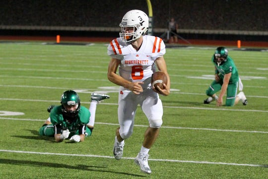 Burkburnett's Mason Duke runs the quarterback keeper for a gain Friday evening in Iowa Park as the Hawks hosted the Burkburnett Bulldogs in 4A action .