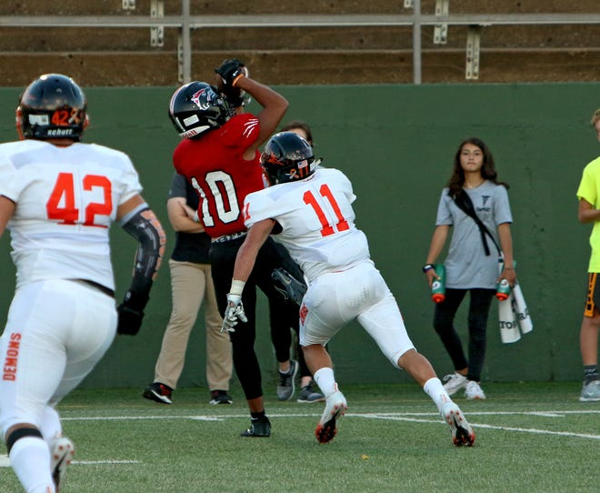 Wichita Falls High receiver Isiah Cherry (10) catches a pass after getting past Dumas' Luis Ramos (11) Friday, Sept. 14, 2018, at Memorial Stadium.