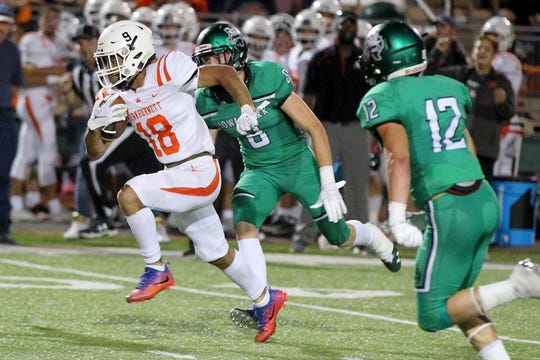 Tre'von Dean of Burkburnett gets the yardage Friday evening in Iowa Park as the Hawks hosted the Burkburnett Bulldogs in 4A action .