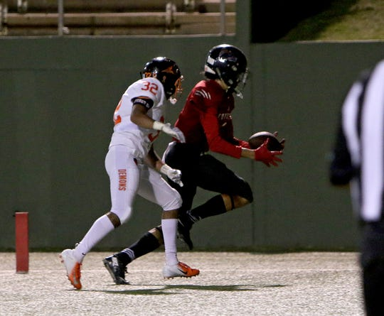 Wichita Falls High receiver Isaiah Johnson (right) bobbles a ball before securing it for a touchdown after catching it over Dumas' Tim Hernandez (32) Friday, Sept. 14, 2018, at Memorial Stadium.