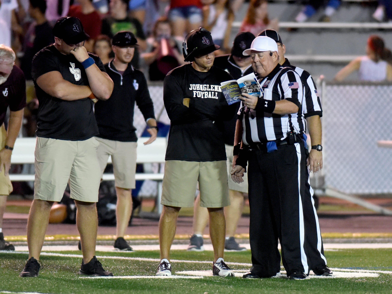 John Glenn coaches Chris Merry, left, and Matt Edwards talk to official Randy Schreiber just before halftime. Philo topped John Glenn, 15-13, on Friday night at McConagha Stadium.