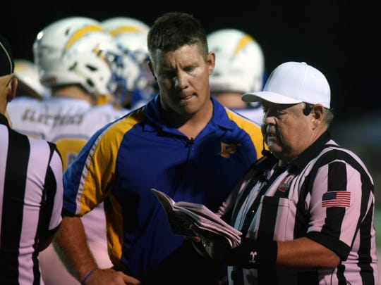 Philo coach Dirk Lincicome listens while official Randy Schreiber explains a ruling just before halftime of the Electrics' 15-13 win against John Glenn on Friday night at McConagha Stadium.