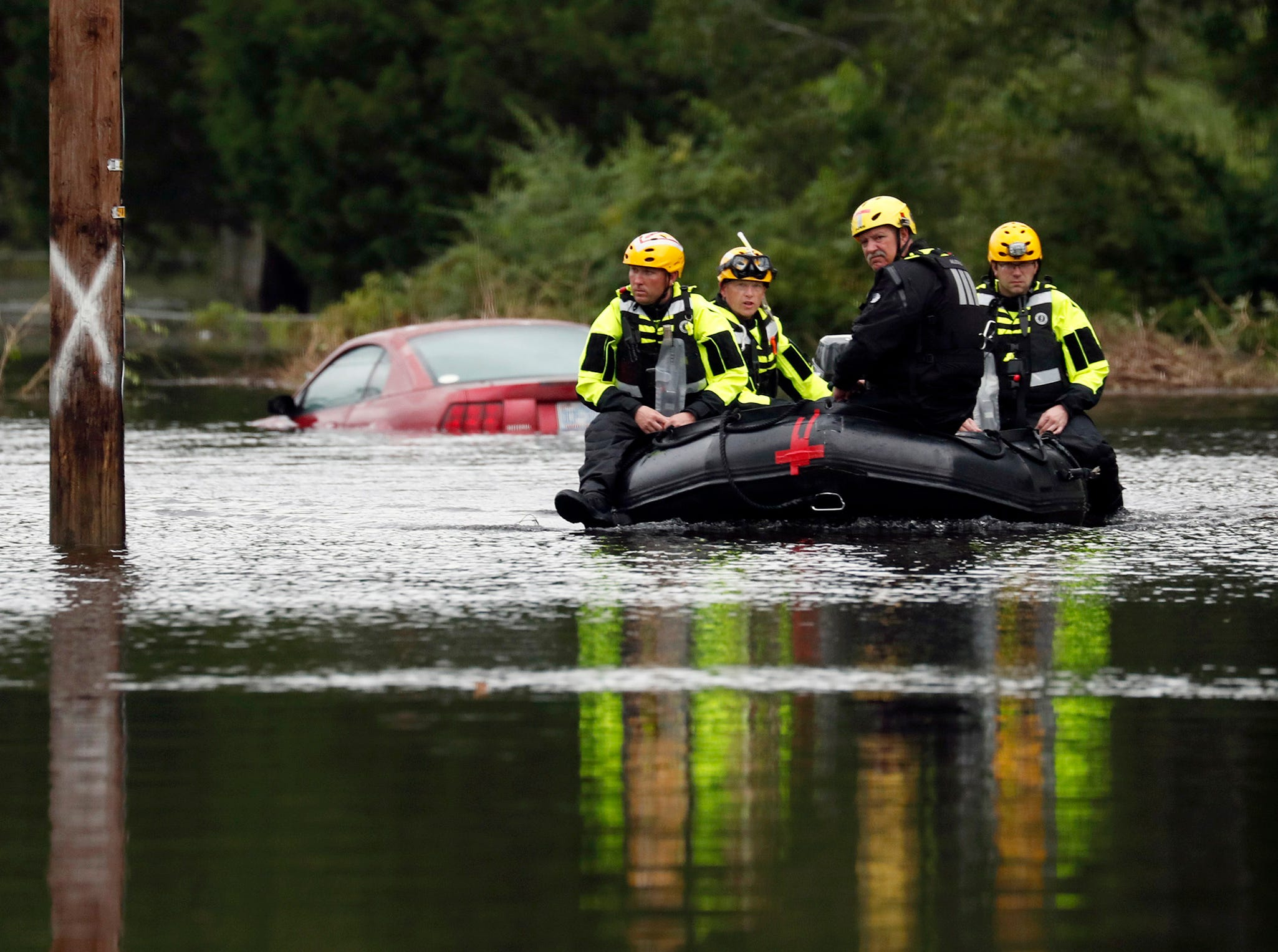 Members of a swift water rescue team check a flooded street caused by the tropical storm Florence in New Bern, N.C., on Saturday Sept. 15, 2018.